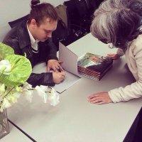 Autor podpisujący książkę
